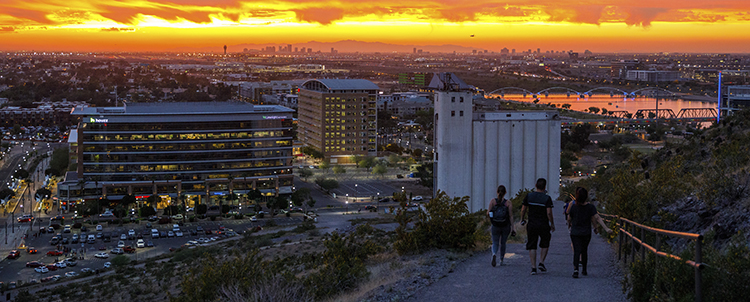 Photo of three students hiking down A Mountain in Tempe at sunset with downtown Tempe in the background
