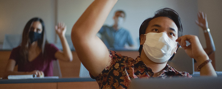 Image of students in facemasks in a classroom with raised hands