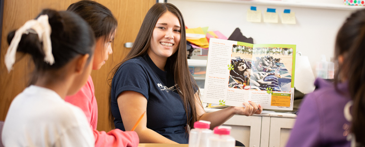 Photo of student teacher showing students a book