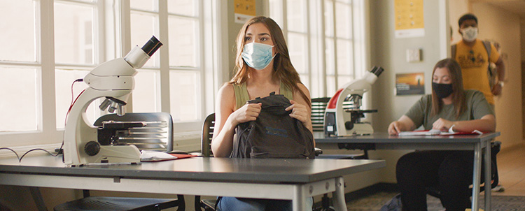 Image of a female college student with a facemask on in a science lab