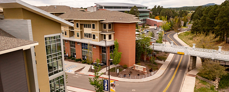 Photo of NAU campus with buildings on the right and a street on the left