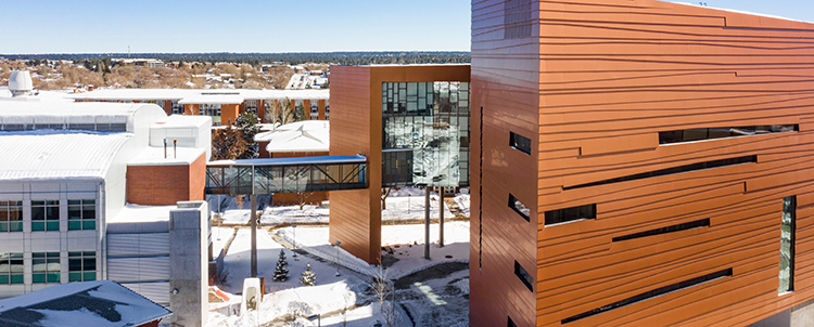Photo of NAU campus with copper buildings in the foreground and snow on the ground.