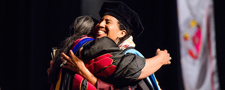 Photo of an Indigenous graduate hugging another person at graduation.
