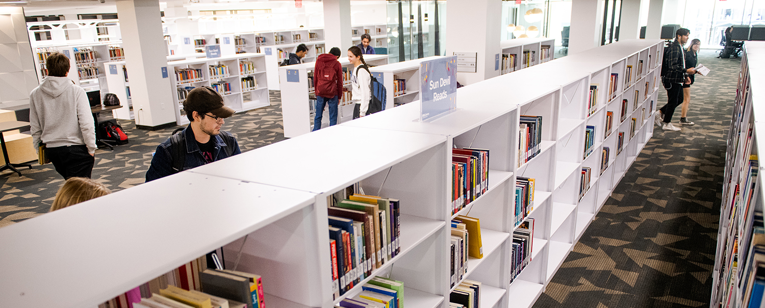 Photo of the interior of a library with students studying and shelves of books