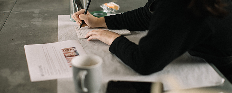 Image of a woman taking notes with a cup of coffee and phone on her desk