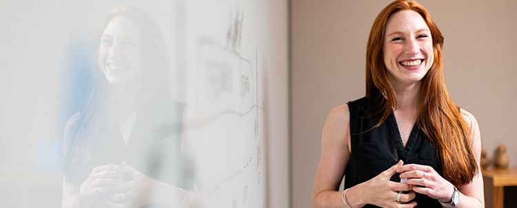 Photo of smiling woman in front of white board