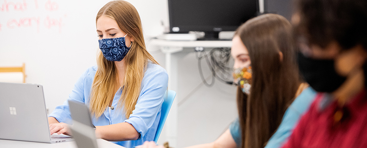 Photo of three students in facemasks working on computers in class