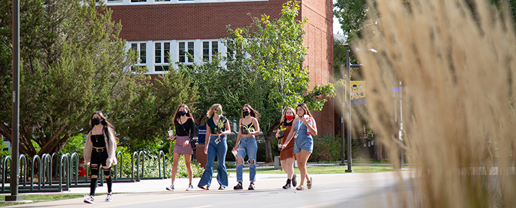 Students walking outside on NAU's campus with facemasks on.