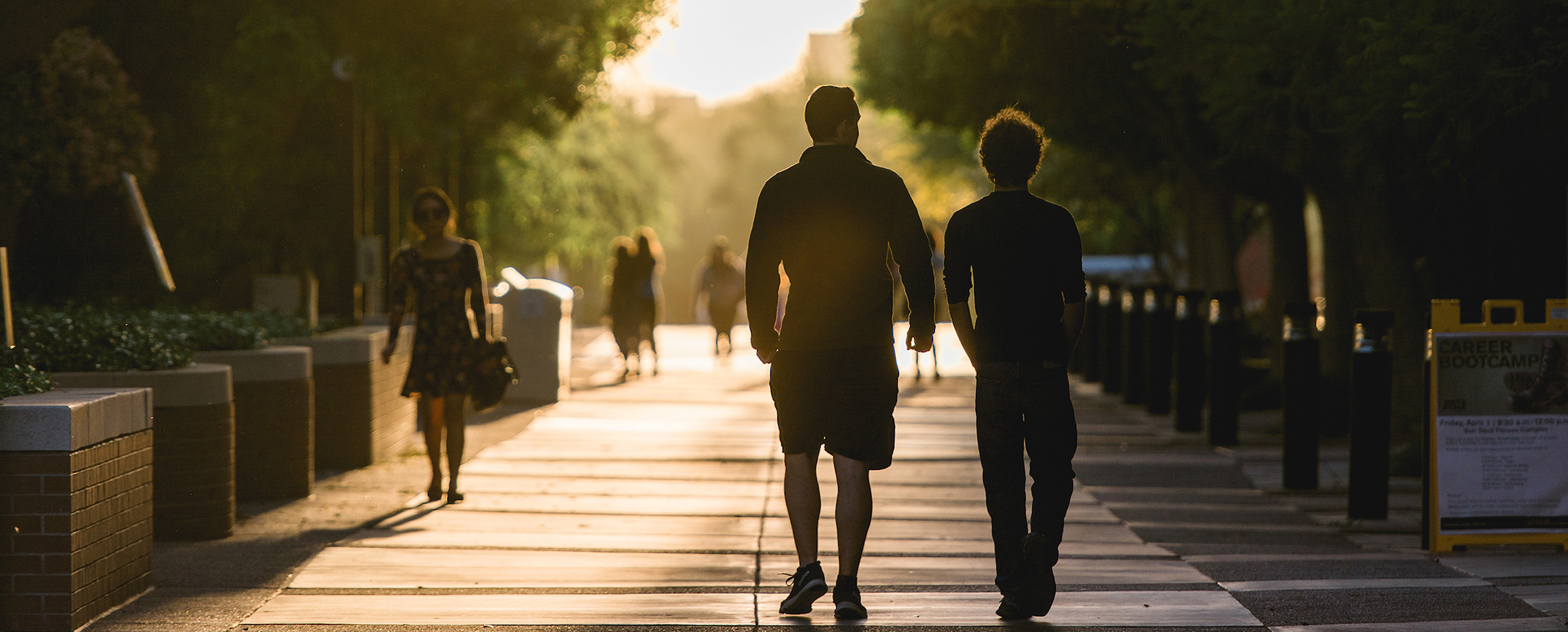 Image of two students walking outside in silhouette.