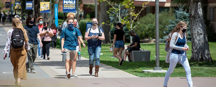 Students walking on campus with facemasks on.