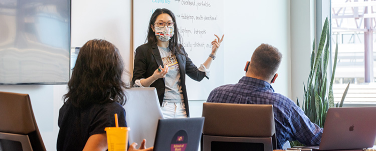 Image of a teacher in front of a classroom with a facemask on with two students with their backs to the camera in the foreground.