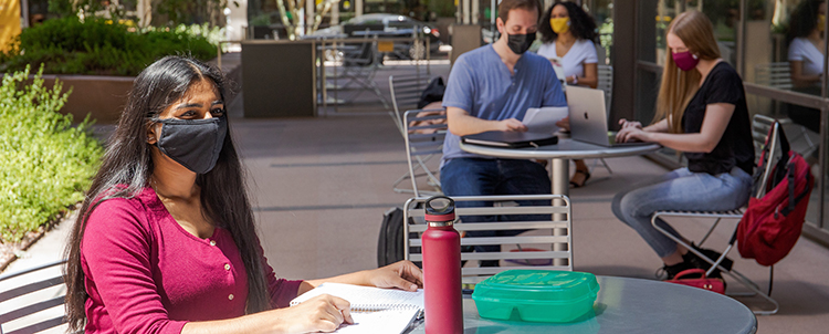 Students studying outside on campus at tables with facemasks on