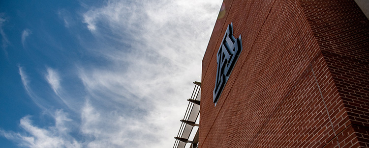 Image of the A on a University of Arizona building with clouds in the sky visible
